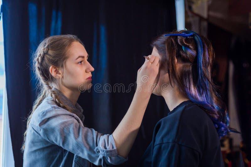 Sminkkonstnär och frisör som arbetar med kvinnaklienten arkivfoton