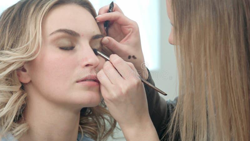 Sminkkonstnär som applicerar ögonfransmakeup till modellögat arkivbild