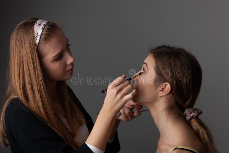 Sminkkonstnär som applicerar ögonskugga runt om ögon av en härlig flicka på grå bakgrund royaltyfri foto