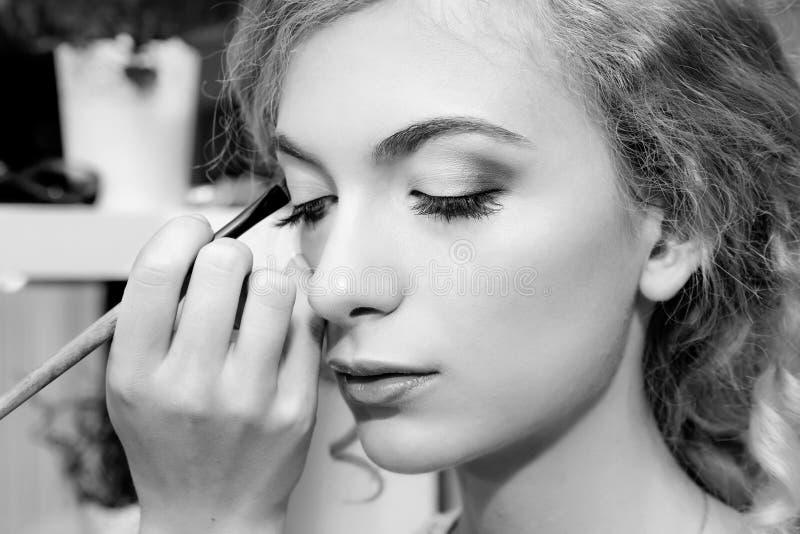 Sminkkonstnär som applicerar färgögonskuggor på modells öga, nära u royaltyfri bild