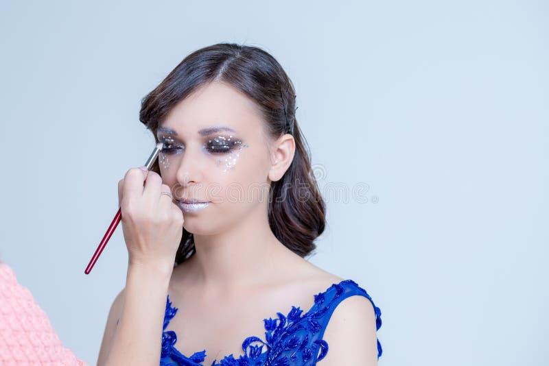 Sminkkonstnär som applicerar ljus färgögonskugga på modells öga Förbereda sig för partiet idérik makeup för flicka inomhus royaltyfria foton