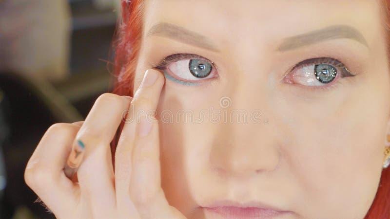 Sminkkonstnär som applicerar makeup till ögat för modell` s Slapp fokus fotografering för bildbyråer