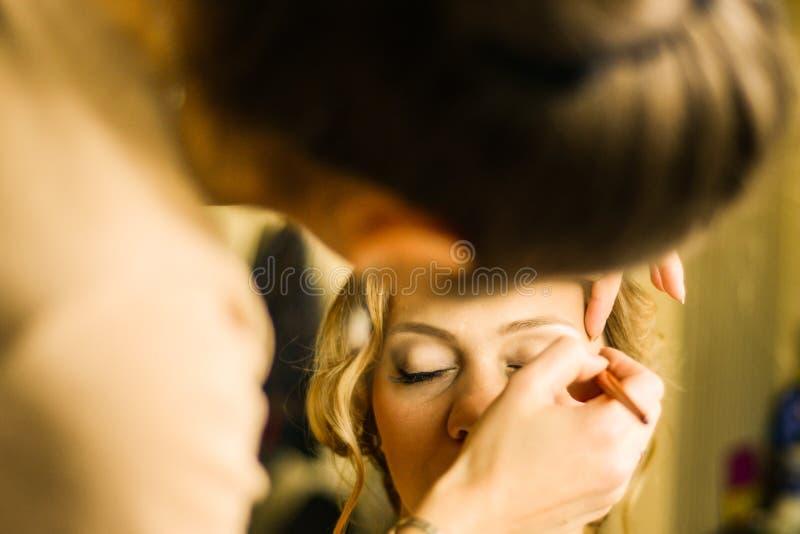 Sminkkonstnär som applicerar upp makeup på modellen, slut arkivbild