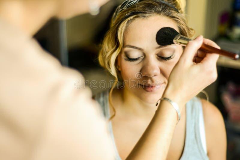Sminkkonstnär som applicerar upp makeup på modellen, slut royaltyfri foto