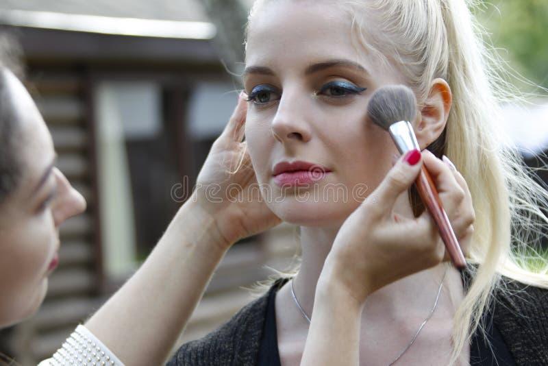 Sminkkonstnär som gör makeup royaltyfri fotografi