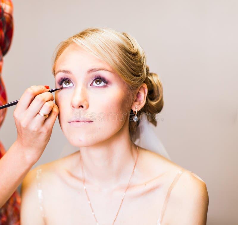 Sminkkonstnär som gör sminket för den unga härliga bruden som applicerar bröllopsmink royaltyfri bild