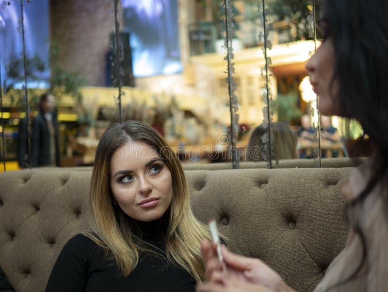 Sminkkonstnär som sitter på soffan och ser flickan med makeup royaltyfri fotografi