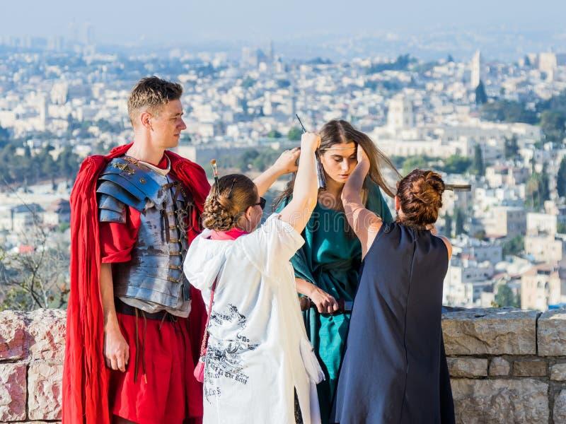 Sminkkonstnären gör makeup för modellen, innan han skjuter på Mt Scopus i Jerusalem i Israel arkivfoto