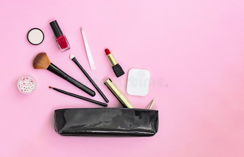 Sminkprodukter som spiller ut ur svarta lackade skönhetsmedel, hänger löst på en pastellfärgad rosa bakgrund arkivbild