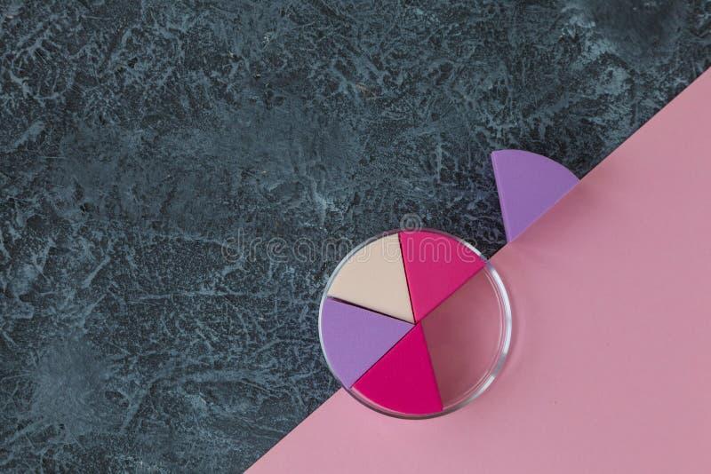 Sminksvampar på mörkerstenbakgrund Kosmetisk applikator Rosa papper med kopieringsutrymme arkivfoton