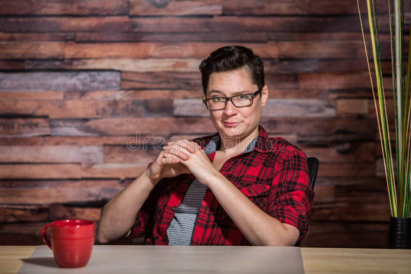 Smirking Boss in Flannel. Smirking woman in flannel shirt with one eyebrow raised stock image