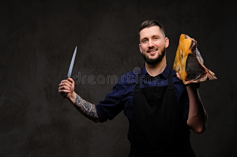 Smirking chef cook holds knife and large piece of exclusive cured meat on dark background. royalty free stock photos