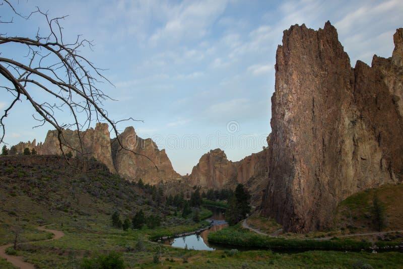 Smith Rock Central Oregon de V.S. Rivier die klippen met boom in de voorgrond tijdens zonsopgang doornemen stock afbeeldingen