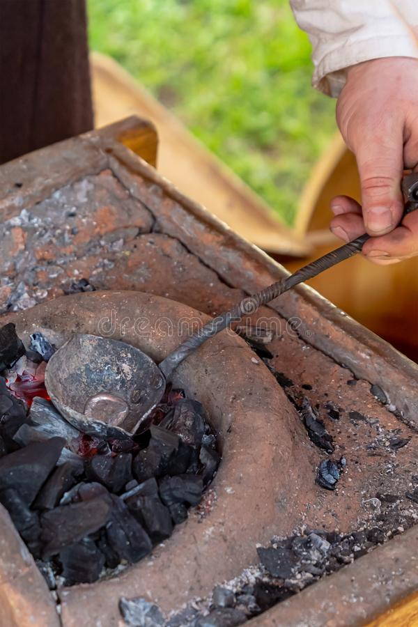 Smith smelting metal tin production bullets against the backdrop of coals bugle clay close-up street production stock image