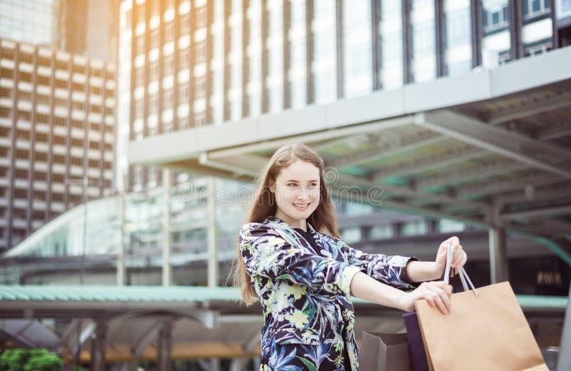smling和拿着在购物中心的美丽的新的年龄妇女画象购物袋 免版税图库摄影