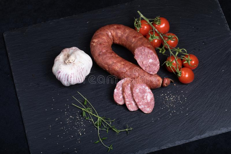 Smocked sausage on black stone plate. Close up of smocked sausage with garlic and cherry tomatoes stock photography