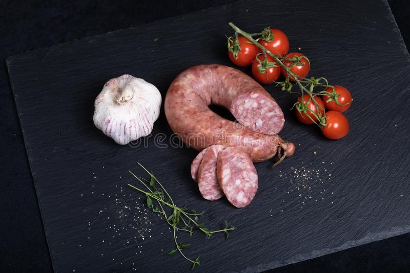 Smocked sausage on black stone plate stock photo