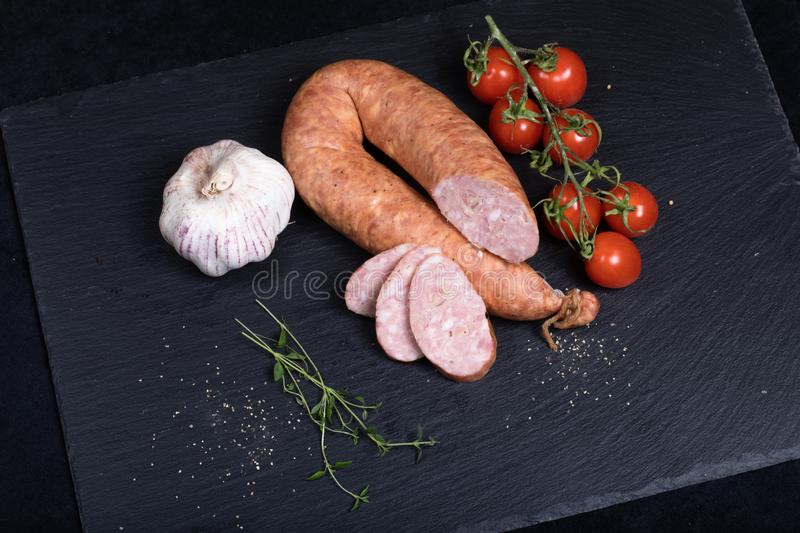 Smocked sausage on black stone plate. Close up of smocked sausage with garlic and cherry tomatoes royalty free stock image