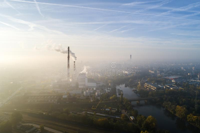 Aerial view of the smog over the city in the morning, smoking chimneys of the CHP plant and the city`s buildings - Wroclaw, Poland royalty free stock photography