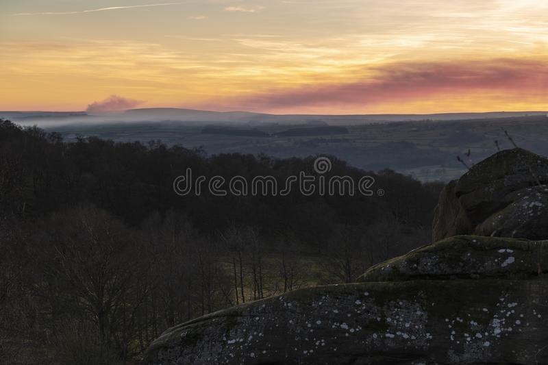 Brimham Sunset. With smoke in the air the sun is setting over the Pennines near Pateley Bridge close to Brimham Rocks stock images
