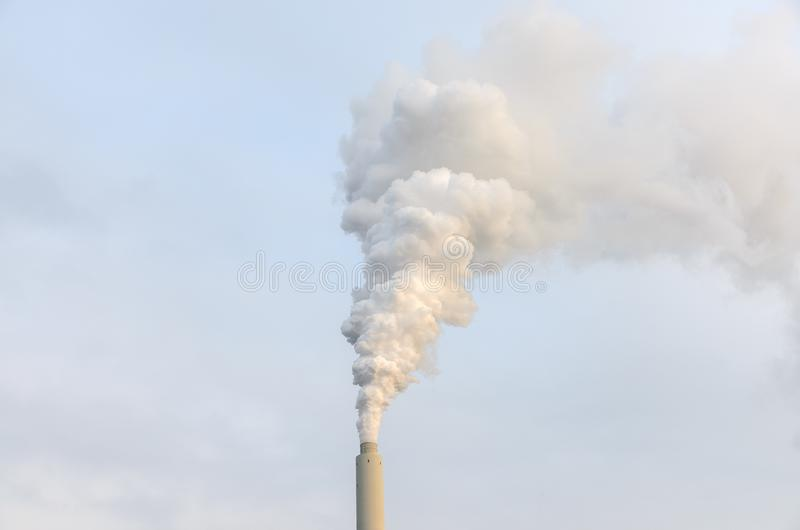 Smoke billowing from an industrial chimney royalty free stock image