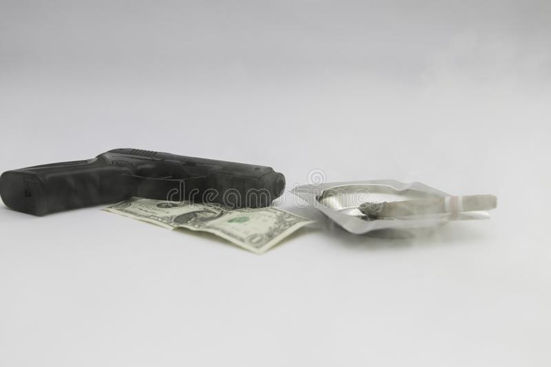 Gun money and cigar separated at the white background royalty free stock photo