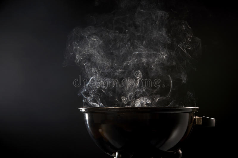 Smoke coming from a hot barbecue fire. In a low angle view of a small circular portable black grill over a dark background with cop space stock photos