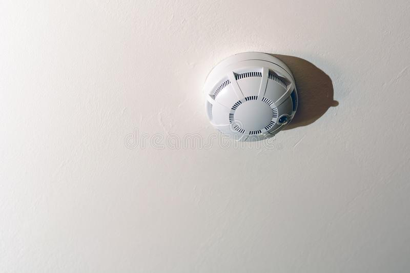 Smoke detector of fire alarm in action stock image