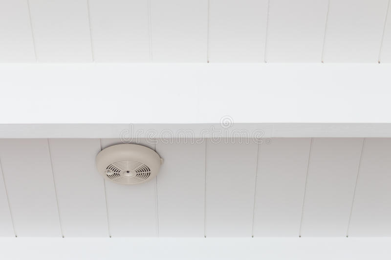 Smoke detector of fire alarm on ceiling. stock images