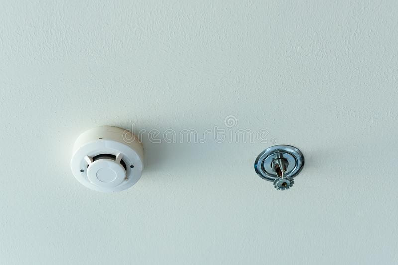 Smoke detector and fire sprinkler on a ceiling. Smoke detector and fire sprinkler on a ceiling royalty free stock photo