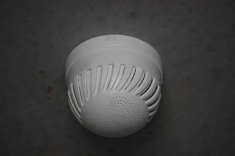 Smoke detector on a gray wall in a new building, fire safety. protection of the apartment or house from fire and smoke. take care stock image