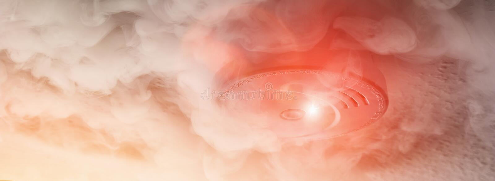 Smoke detector with smoke. A smokedetector detects smoke with a red warning light in a action on a roof. ideal for websites and magazines layouts stock photo