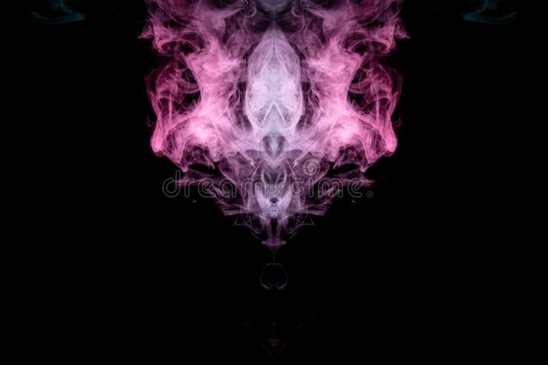 Smoke of different blue, red and pink colors in form of horror in the shape of the head, face and eye with wings on a black royalty free stock photography