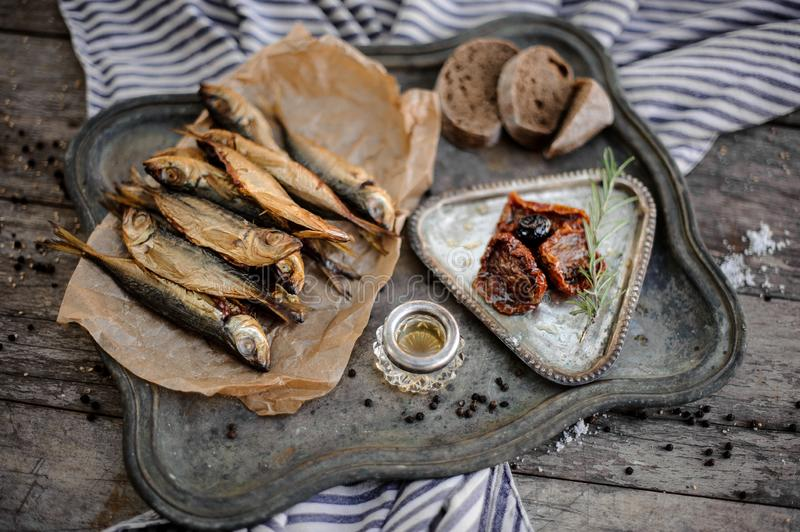 Smoke-dried horse mackerel fish on the paper on the metal tray with a sun dried tomatoes, oil and bread. On the grey striped napkin on the wooden table stock photo
