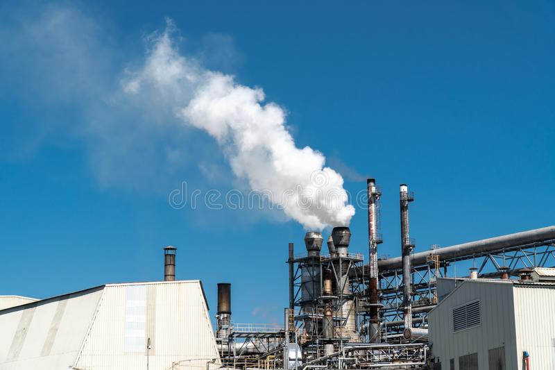 Smoke emission from factory pipes. On blue sky stock photos