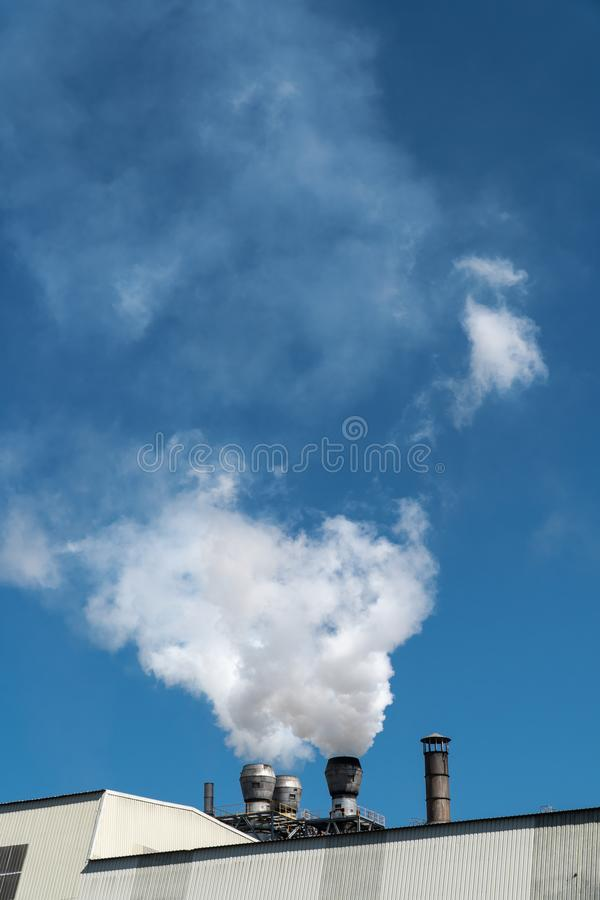 Smoke emission from factory pipes. On blue sky royalty free stock photo