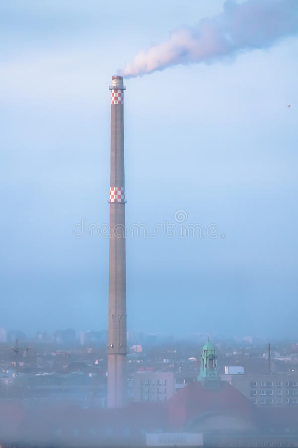 Smoke from a factory chimney in a hazy urban sky stock photos