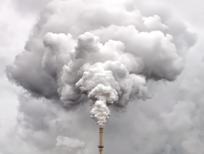 Smoke from factory pipe against overcast sky stock photos