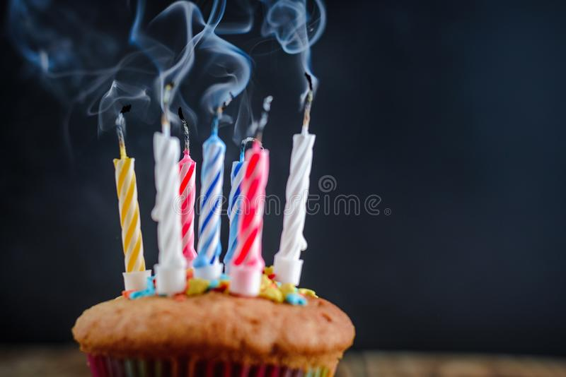 Smoke from faded festive candles on cupcake stock images