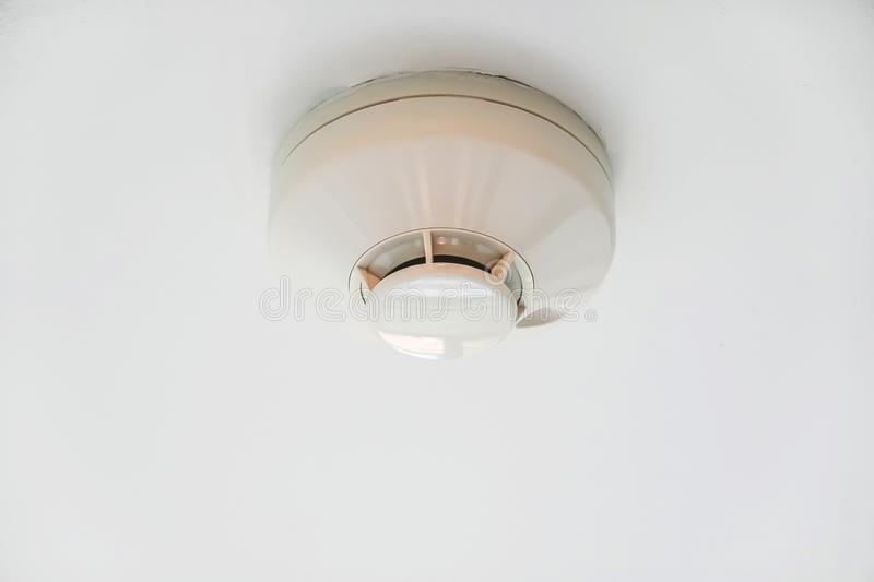 Smoke fire detector mounted on roof. In condo stock images