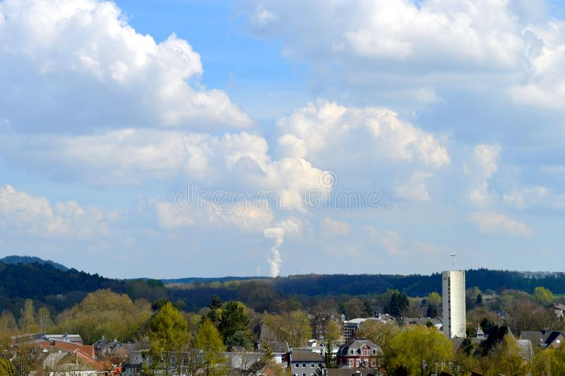 Smoke that forms a cloud. Smoke/ Steam from a factory that forms a super nice cloud above the village of Herzogenrath in Germany royalty free stock photo