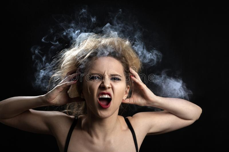 Smoke on head. Stressed woman with cloud of smoke on her head on black background stock images