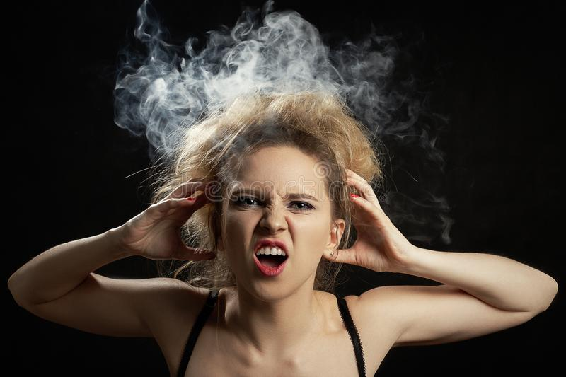 Smoke on head. Stressed woman with cloud of smoke on her head on black background royalty free stock photo