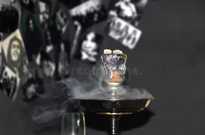 Smoke hookah on a grey background with a beautiful smoke. Smoke hookah with a beautiful smoke against a dark background royalty free stock photo