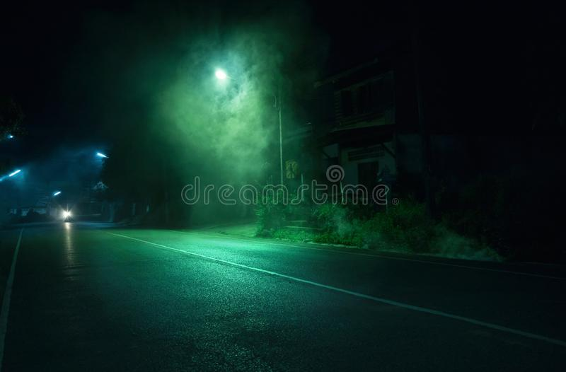 Smoke near street light on public road with old abandoned house background in Trang Thailand. Horror scene stock image