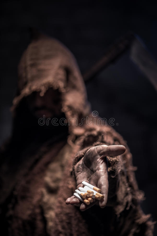 Smoke this nicotine and you will die. Frightful death character is proposing you a cigarette. He is standing in darkness and waiting for victim royalty free stock photography