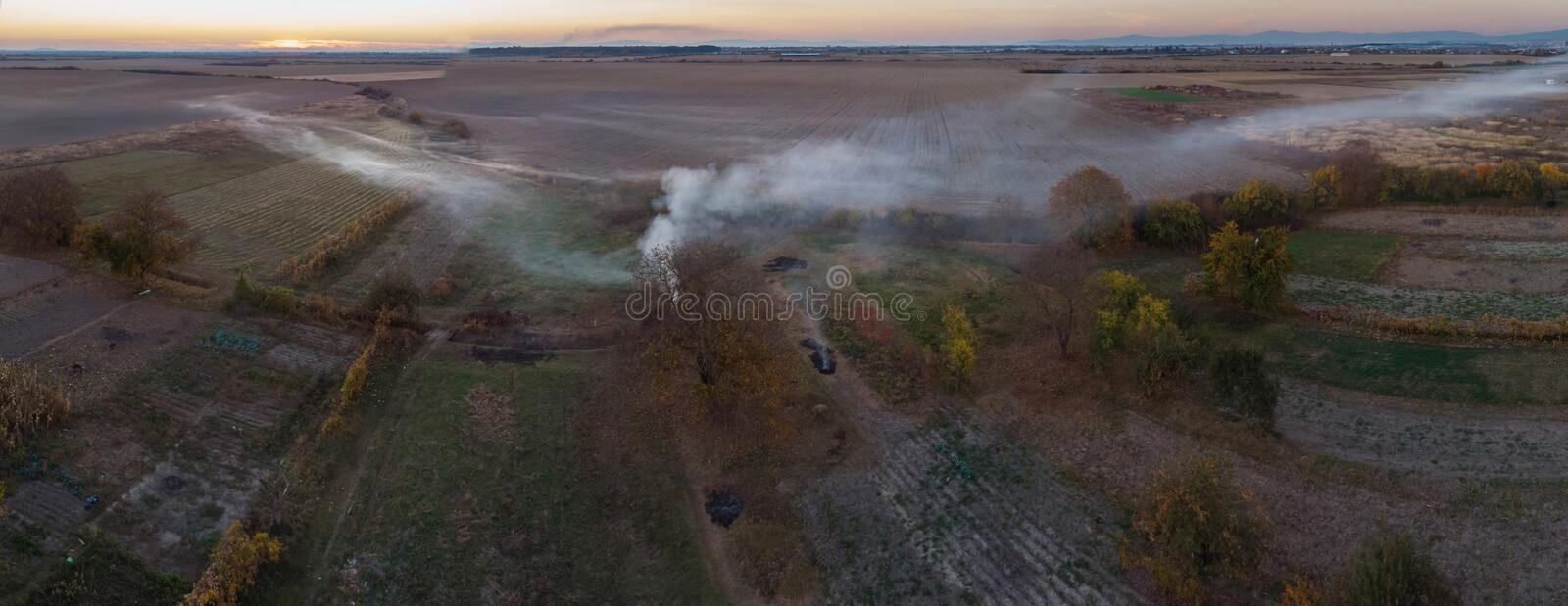 The smoke over the village. Clubs of smoke over the village houses and fields. stock photo