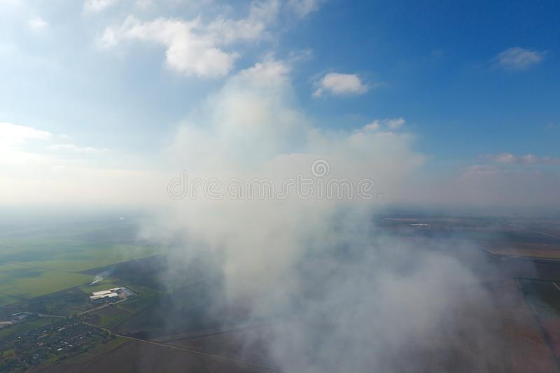 The smoke over the village. Clubs of smoke over the village houses and fields. Aerophotographing royalty free stock images