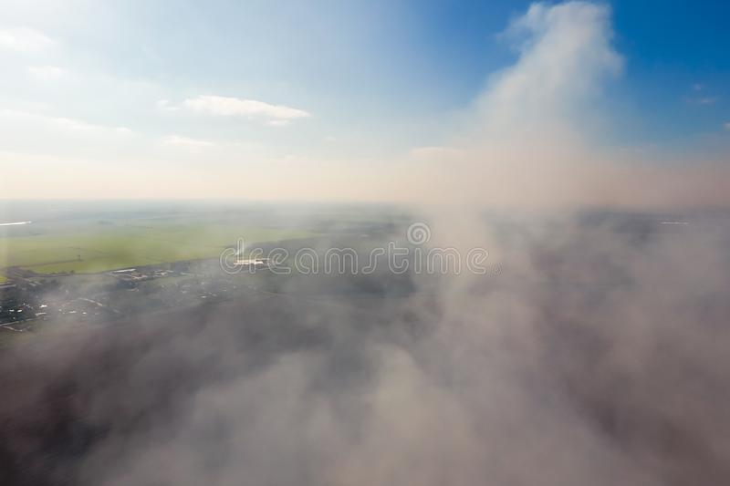 The smoke over the village. Clubs of smoke over the village houses and fields. Aerophotographing royalty free stock photo