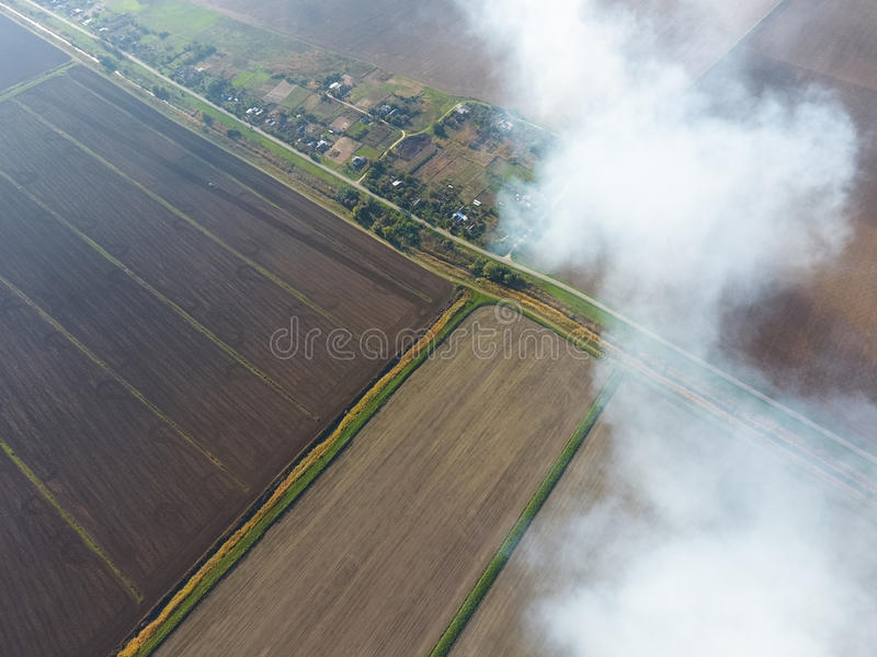 The smoke over the village. Clubs of smoke over the village houses and fields. Aerophotographing areas stock photography